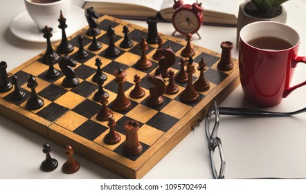 Wooden desk with chess play, book and two cups of coffee on white table. Board game for two, intelligence and brain upgrade concept