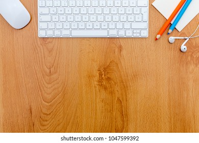 Wooden desk with computer keyboard and office supplies.