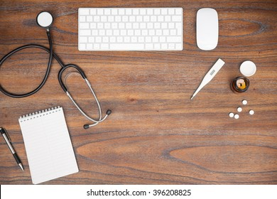 Wooden desk with a computer, notepad, stethoscope and some pills in a physician's office