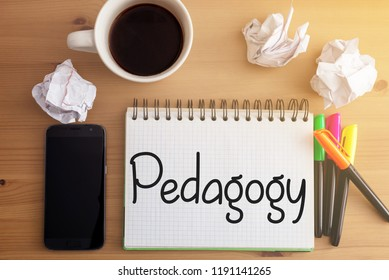 Wooden desk with crumpled paper, hot coffee, smartphone and notebook with handwritten words related to education: Pedagogy
