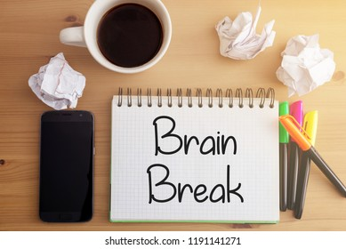 Wooden desk with crumpled paper, hot coffee, smartphone and notebook with handwritten words related to education: Brain Break