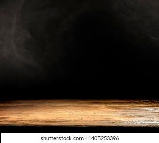 Der Holzschreibtisch ist frei für die Dekoration. Schwarzer Hintergrund mit Platz für Ihren Text. Rauchen und Stimmungsbild.
