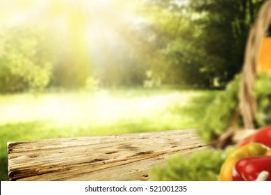 Wooden desk of free space for your decoration of product or text with spring background of garden and blurred fresh vegetables