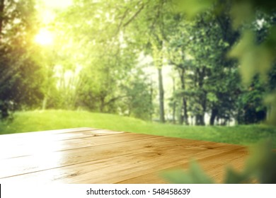 wooden desk in garden and free space for your decoration with spring trees and leaves