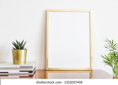 Wooden desk with gold poster frame mock up, mags and succulent plant.