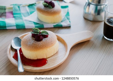 Wooden desk with Japanese cheesecake and cup of coffee in morning, Close up.