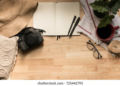 Wooden desk with journal, coffee mug, pens, hat, DSLR camera top view with copy space