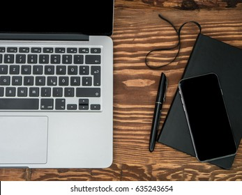Wooden Desk with Laptop, notebook and smartphone. Top-view
