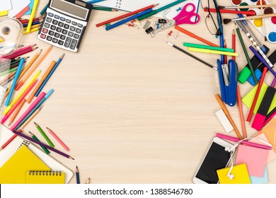 Wooden desk messed with stationery workplace top view nobody empty space