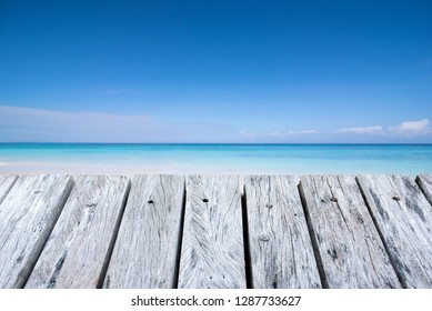 Wooden desk or plank on sand beach in summer. background. For product display.