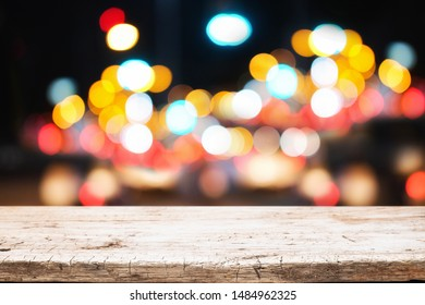 Wooden desk space and blurred night light bokeh background. product display template