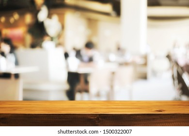 Wooden Desk space and blurry background of restaurant vintage tone for product display montage.