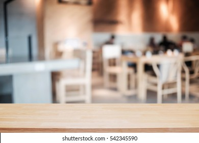 Wooden desk space over blurred resturant or coffee shop background for product display montage