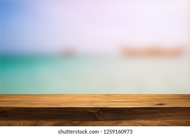 Wooden desk space over summer sea side sunny day background. Product display montage