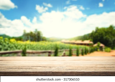 wooden desk space platform and farm of field background vintage tone.