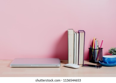 Wooden desk table with pink wall with copy space,laptop, supplies and coffee mug. Front view workspace and copy space