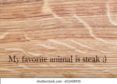 Wooden desk with a text: my favorite animal is steak