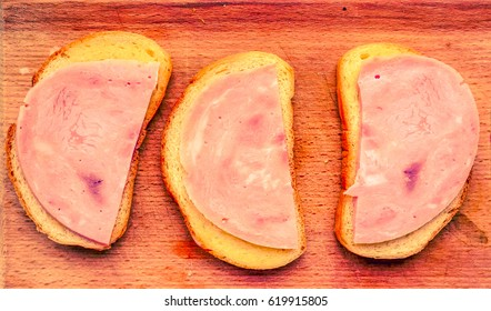 wooden desk with three morning sandwiches made with white bred, some butter and thin peaces of sausage. sandwiches with ham as part of breakfast