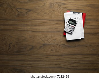 wooden desktop with calculator and invoices