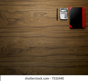 wooden desktop with calculator pen and book