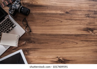 wooden desktop and professional photographer working with a laptop