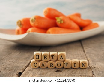 Wooden dices with the German words beta carotene and fresh carrots in the back, healthy eating concept