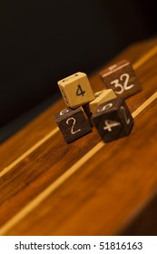 Wooden dices with numbers on wooden surface.