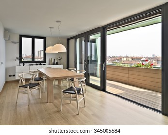 wooden dining table and chairs in the attic with a view of the city skyline, the flooring is made of natural wood