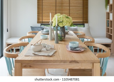 wooden dining table in modern dining room with table set and vase of plants, interior design concept