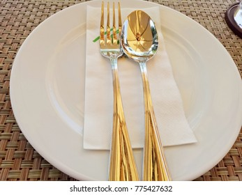 Wooden dining table with prepared dishes, utensils, cutlery and glass.