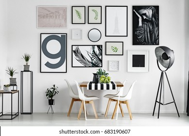 Wooden dining table with tablecloth by white wall with pictures
