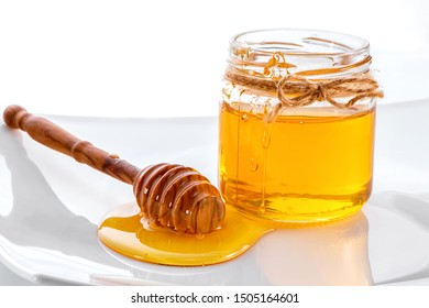 wooden dipper next to jar of honey decorated with bow of twine close-up on porcelain plate against white background