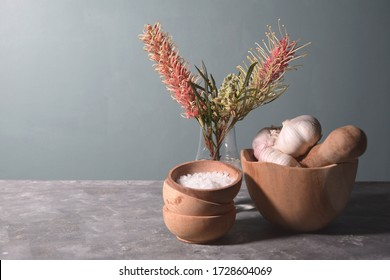 Wooden dishes, garlic and salt with a pink bottle brush flower on a dark background. Rustic food style image.