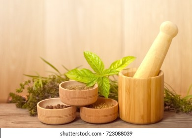 Wooden dishes with a pestle, surrounded by cups with pepper, cumin, coriander, fragrant greens. Composition of aromatic herbs and spices in wooden utensils.