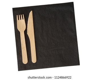 Wooden disposable cutlery on black serviette. Isdolated on white. Ecofriendly.