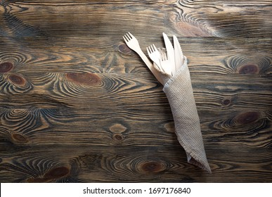 Wooden disposable forks and knives in a linen napkin on the table. Above, copy space