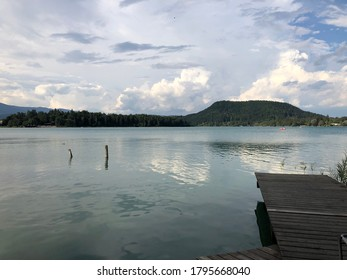 Wooden dock at beautiful lake in Austria with mountains and cloudy sky in the back