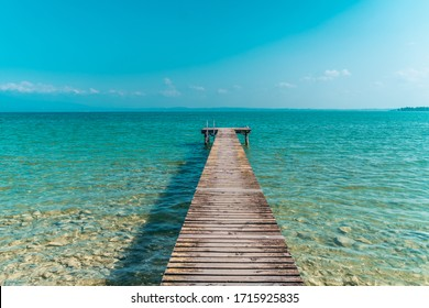 Wooden dock for boats on the light blue sea in a beatiful sommer day - Shutterstock ID 1715925835