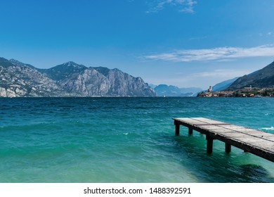 Wooden dock jutting out into the turquosie water of Lake Garda. the village of Malcesine