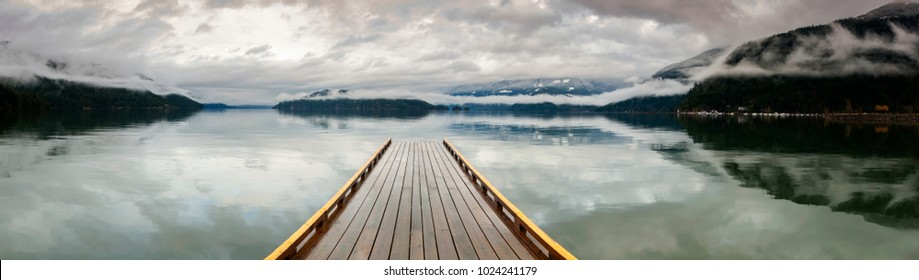 Wooden Dock on Harrison Lake, British Columbia, Canada. A dock appears to be heading out to nowhere on a lake in the Pacific Northwest. Harrison Hot Springs Resort.