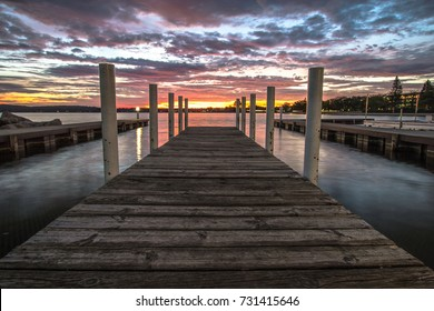 Wooden Dock On Sunrise Lake. Summer sunrise over the waters of Grand Traverse Bay in Traverse City, Michigan. Shot with long wooden dock in foreground sunrise over water at horizon.