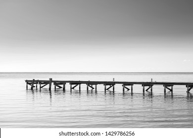 Wooden dock over calm ocean water as minimalism background in stunning black and white