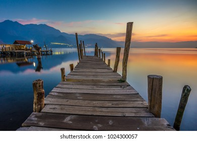 Wooden dock over Lake Atitlan in San Juan La Laguna, Atitlan, Guatemala at sunrise.  Dawn over the lake with morning and sunrise sky.