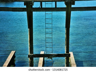 Wooden dock pillars and ladder with blue water in the background.