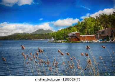 Wooden dock with yachts on the blue lake and behind him is stone castle on the hill and blue sky.