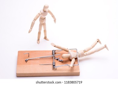 Wooden doll caught in a mouse trap and bystander in front of white background