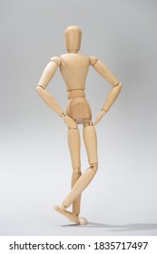 Wooden doll with hands on hips on grey background,stock photo