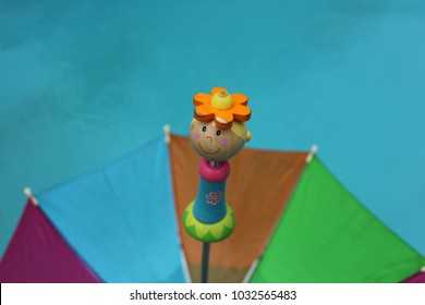 Wooden doll on umbrella handle close up