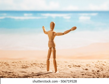 Wooden doll with open arms is worth on the seashore.