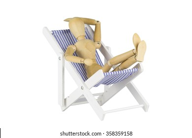 A wooden doll is posing on a miniature beach chair isolated on white